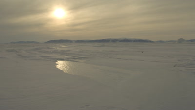 Wide angle sea ice with landmass behind and moody arctic sun dipping but not setting along the horizon at Grise Fjord