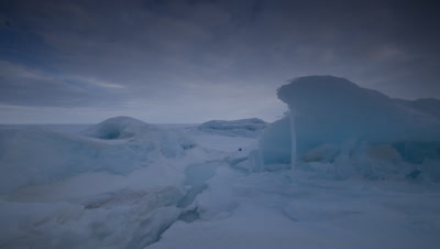 Close up sea ice with cold blue clouds racing away from camera at Grise Fjord