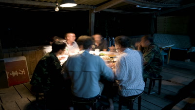 Medium wide angle group of people 6 Chinese and 2 Westerners sharing a meal at a round table in simple hut