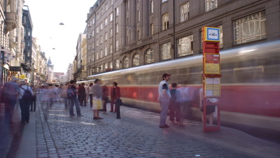 Medium wide angle looking along cobbled Prague city street with elegant buildings, featuring tram stop and commuters in f/g