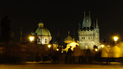 Medium wide angle from middle of Charles Bridge looking towards Old Town, buzzing and crowded with people crossing bridge