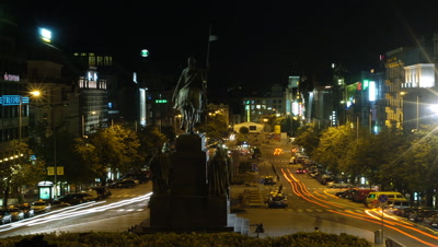 Medium wide angle looking down Wenceslas Square from behind statue of Wenceslas f/g with traffic streaming around square