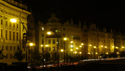 Medium wide angle floodlit terrace of grand buildings with streaming motion blur red car lights passing in front (adjacent to river)