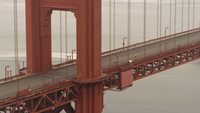 Mid shot red tower of Golden Gate Bridge with view of road and traffic flowing across - taken from shore