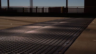Close up road deck on Golden Gate Bridge with cars constantly wiping frame