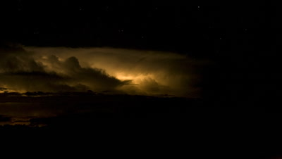 Medium wide angle black sky with golden cloud illuminated by blanket lightning