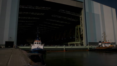 Medium wide angle entrance to dry dock, now filled, as ship is brought out by two tug boats at Aker Ship yard