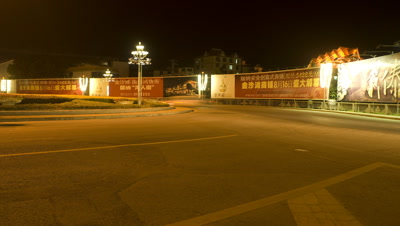 Low wide angle well lit roundabout with traffic flowing around featuring large Chinese poster