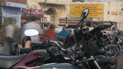 Medium wide angle motorbike park outside market with motorbikes and pedestrians coming and going