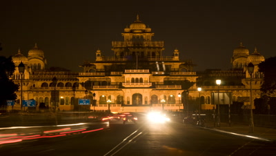 Medium wide angle from centre of road looking to the floodlit Central Museum with busy traffic as evening becomes night
