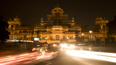 Medium wide angle tilt down from sky to reveal the floodlit Central Museum with busy traffic at night