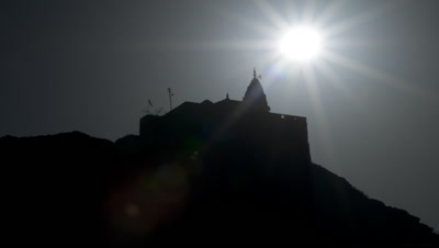Medium wide angle sun rises behind and over silhouetted Hindu Sun temple on hill
