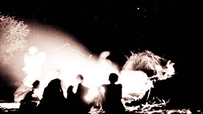 Sepia medium wide angle tribal people San bushmen gathered around a campfire in the bush with big sky and stars