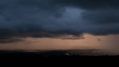 Wide angle dark black rainclouds dropping rain move over open valley landscape with many rivers