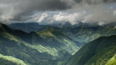 Wide angle cloud shadows and streaming rain clouds over lush green forested mountain range with cloud wipe