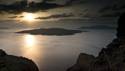 Wide angle sun sets over wind blown sea into dark clouds racing over Santorini caldera