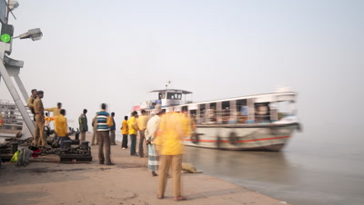 Medium wide angle Ganges River quayside with river ferries arriving and leaving and passengers embarking and disembarking