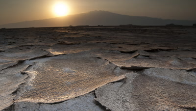 Low wide angle - from black - sun rises from behind mountain to reveal dry cracked flakes of caustic mud