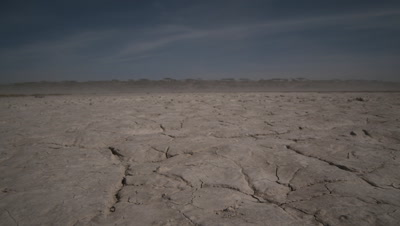 Wide angle dry cracked mud with clouds of dust blowing behind and blue sky