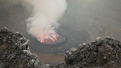 Mid shot Nyiragongo's bubbling lava lake with plumes of steam issuing from lake over the volcano rim