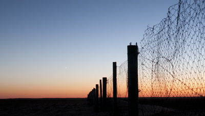 Wide angle chain link fence disappearing off to far horizon as horizon glows orange then turns black