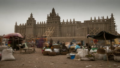 Medium wide angle busy market in front of largest mud structure in world, Djenne mosque as sun comes up from darkness