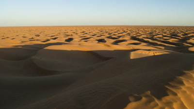 Wide angle dawn shadows over vast golden sand sea of Sahara dunes of disappearing into horizon