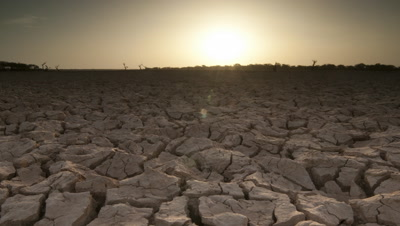 Wide angle sun rises over dry cracked earth
