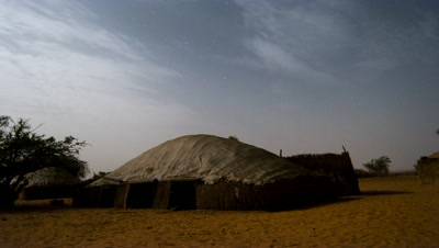 Medium wide angle from night sky the day dawns over Tuareg desert nomad tent in sandy desert