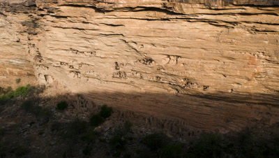 Big wide angle shadow moves down cliff escarpment and lights up Dogon cave houses in cliff face