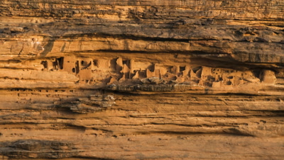 Wide angle shadow moves across cliff face and lights up Dogon cave houses in cliff escarpment