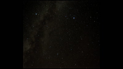 Wide angle black starry night sky moves overhead with satellite