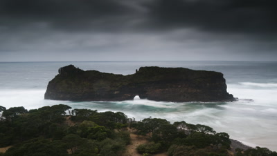 Medium wide angle dark skies and stormy sea rushing through and around the Hole in the Wall rock formation off the Eastern Cape