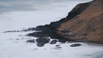 Medium wide angle constant waves beating the rocky shore line along the Eastern Cape