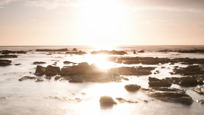 Wide angle orange sunrise over rocky shoreline with fast moving cloud and god rays penetrating through