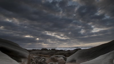Wide angle dawn over smooth worn rocky shoreline looking out to stormy sea with threatening clouds racing away offshore