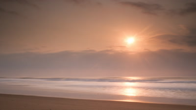 Wide angle soft pink orange sun rises over sea with waves gently lapping the sand