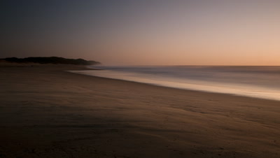 Wide angle pan over sand towards sea at dawn with waves lapping the shore and sun on sparkly water