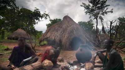 Mid shot Suri tribe, women with lip plates and children, sitting around cooking fire in their village