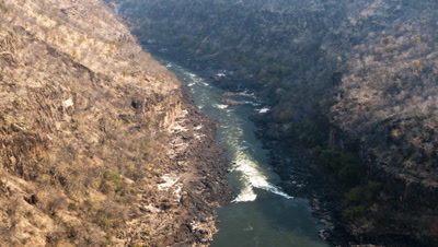 Wide angle top shot of Zambezi RIver rapids at bottom of Batoka Gorge as shadow moves across gorge and fades to black