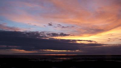 Wide angle blue and orange dawn clouds as sun rises over Etosha salt pan