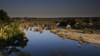 Wide angle top shot bend in the Boteti River as moon sets and day dawns