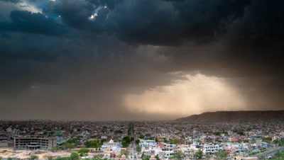 Wide angle dramatic monsoon clouds dropping showers of rain over Jaipur city then sun and beautiful god rays appear
