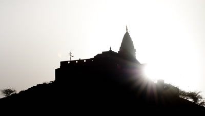 Medium wide angle sun rises, bursting out from behind Sun Temple at Galta