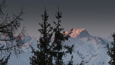 Medium wide angle snow covered peaks as sun goes down reflecting pink light onto snow