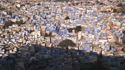 Wide high angle of Jodhpur rooftops with mountain shadow moving across then sun lights the city