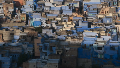 Medium wide angle of blue Jodhpur houses and rooftops as mountain shadow moves across and sun lights the city