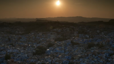 Wide angle over blue Jodhpur houses and rooftops and surrounding hills as orange sun sets