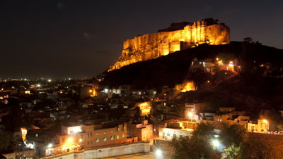 Wide angle view over Jodhpur rooftops towards the floodlit Fort at sunset