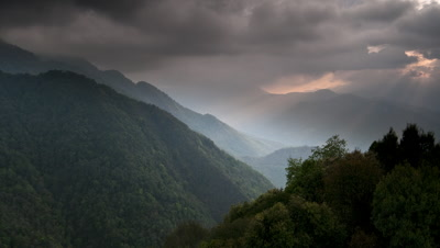 Medium wide angle monsoon storm clouds and god rays stream over forested hills in Nagaland bordering Burma